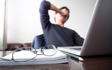 man with his hand holding his face taking a brake from working with laptop computer and notebook with eye glasses on wooden desk. concept of stress/rest/tension/failed/discourage